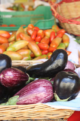 Fresh light and dark eggplants on the background of oblong tomatoes on the counter of the vegetable market