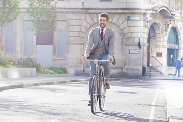 Young man in suit riding bicycle on city street