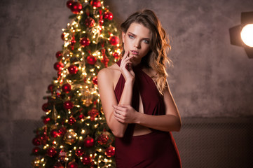 Portrait of sexy girl in beautiful red dress. New year's feeling. Merry christmas