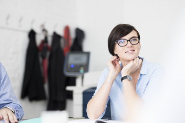 Businesswoman with glasses listening in meeting