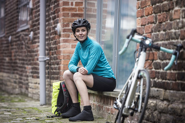 Female cyclist sitting by bicycle on brick wall