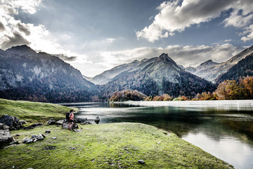 Young woman hiking by lake and mountain