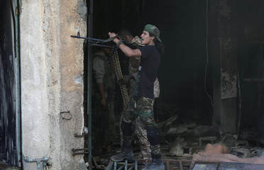 A member of the Libyan National Army reacts as he holds his weapon during clashes with Islamist militants in Khreibish district in Benghazi