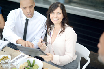 Businesswoman greeting colleague with handshake at restaurant