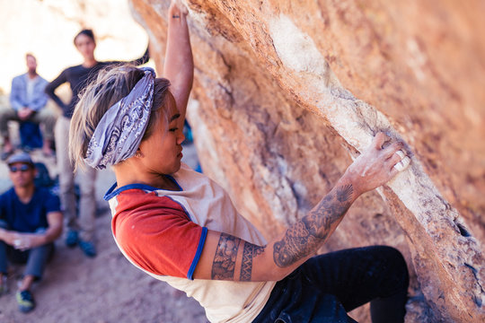 Petite asian woman rock climbing outdoors hangs from stone overhang with people watching