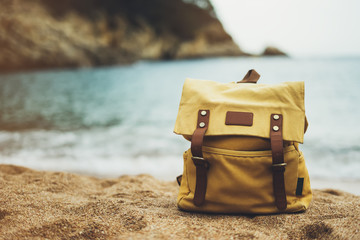 Hipster hiker tourist yellow backpack closeup on background sea enjoying sunset ocean horizon, blurred panoramic seascape sunrise blank mockup, traveler holiday concept, sunlight view in trip vacation