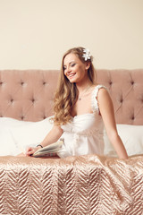 Photo of happy girl in white negligee sitting on bed