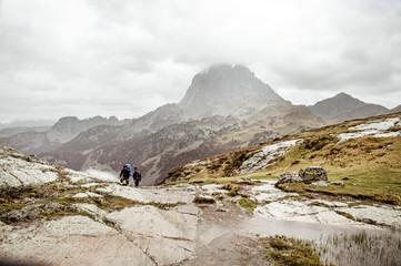 Young men hiking on mountain during overcast day