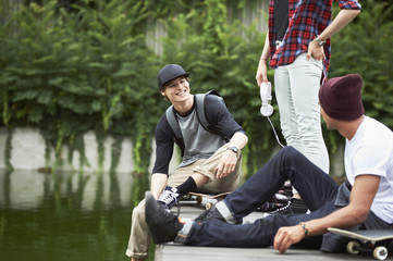 Teenage friends on jetty with skateboard