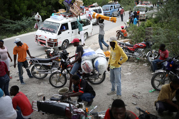A man drives a motorbike loaded with sacks back to the road as trucks block the road to the border with the Dominican Republic, in Malpasse