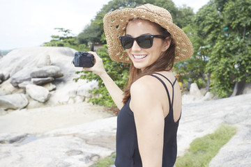 Young woman wearing sunglasses holding camera on rock