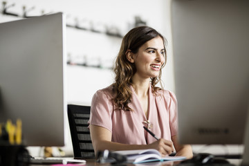Smiling young businesswoman writing notes at desk