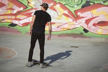 Teenage boy with skateboard in skatepark
