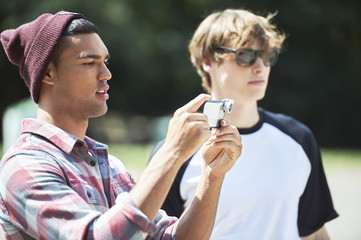 Teenage boy taking photograph with smartphone
