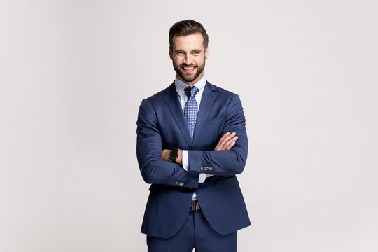 Handsome and successful. Handsome young man keeping arms crossed and looking at camera with smile while standing against white background.