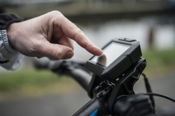 Hand of man pressing GPS navigator on bicycle