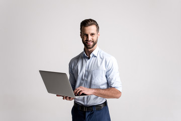 Working with joy. Handsome young man using his laptop and looking at camera with smile while standing against white background. Wall mural