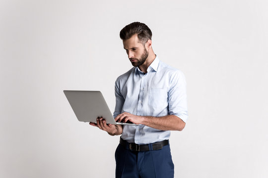 Having some emails to look through. Handsome young man using his laptop while standing against white background.