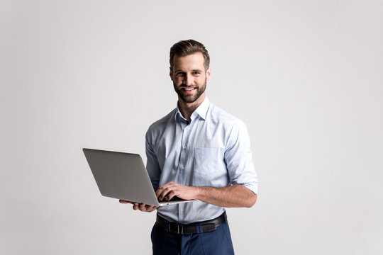 Working with joy. Handsome young man using his laptop and looking at camera with smile while standing against white background.