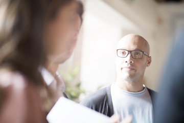 Businessman with glasses listening to colleague in office
