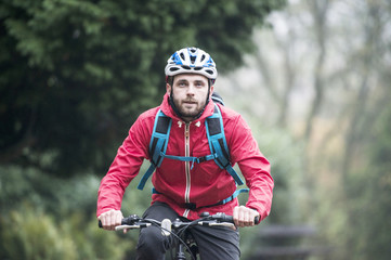 Man in red jacket commuting by bicycle