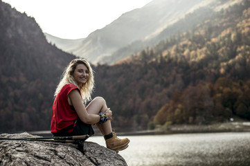 Young woman hiker resting on rock beside lake