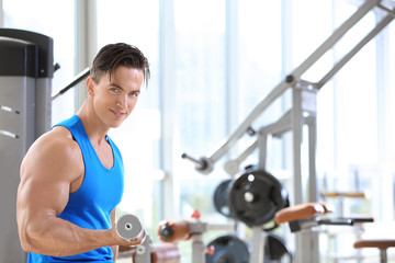 Muscular young man training in gym