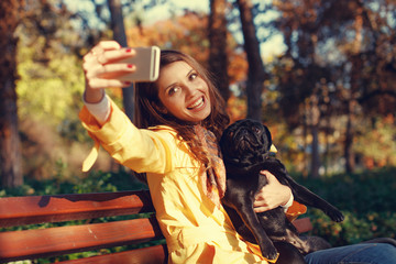 Young woman doing selfie with her pug dog in the park