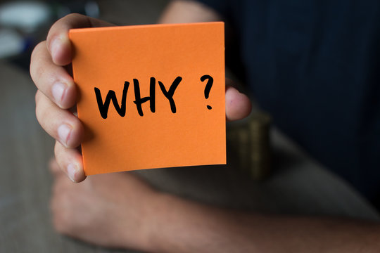 Hand holding an orange Paper with the word why - Why?, Business Concept