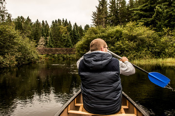 Man canoeing with Canoe on the lake of two rivers in the algonquin national park in Ontario Canada on cloudy day
