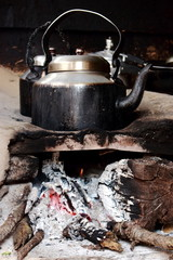 Old metal smoked pot on wooden campfire while cooking tea in rustic outdoor indian kitchen.