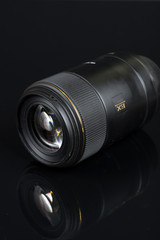 DSL camera lens isolated above black background with reflections