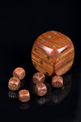 Brown wooden dices with dots isolated above black background wit
