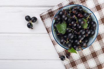 Fresh blackberries (black currant) in ceramic bowl on white wooden table, flat lay
