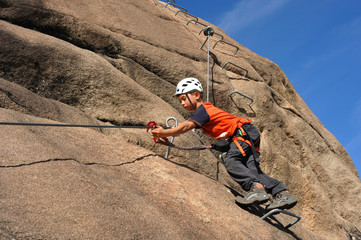 6-jähriger Kletterer beim Umhängen der Selbstsicherung im Klettersteig Via Ferrata dei Picasass bei Baveno am Logo Maggiore, Italien