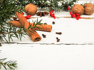 Cinnamon sticks, nuts, spices, berries on vintage wooden background.