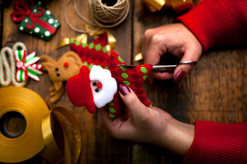 Hands of woman decorating Christmas gifts and decorations