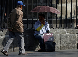 A worker of plumbing waits for work outside the Metropolitan Cathedral at Zocalo Square in Mexico City