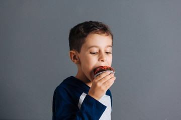 Brazilian child eating cupcake on gray background