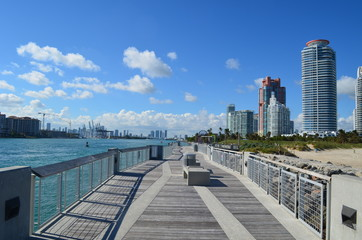 Southpointe Park fishing pier,Port of Miami loading cranes,Miami tall building skyline and luxury condominiums overlooking the park and beach.