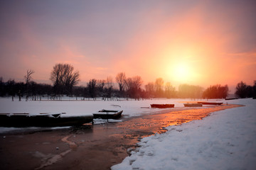 Beautiful winter sunset at the river. The boat in snow at the river in the winter