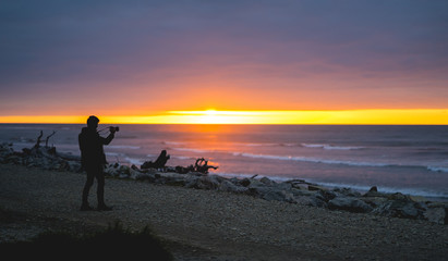 Silhouette of the man taking a photo on the sunset