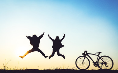 silhouette of young woman and boy jumping on sunset sky with bicycle on the prairie at yellow evening horizon sea yellow sunset heaven background Outdoor.