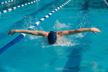 Teen female athlete competing in the butterfly stroke competition in a swim meet