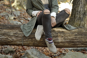 Girl is sitting in autumn forest in the mountains. Hiking and traveling