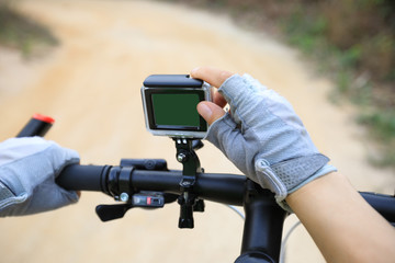 cyclist hands set the action camera mounted on mountain bike