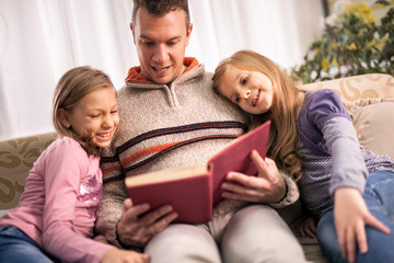 happy family father and children reading a book