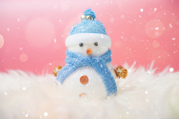 Happy snowman standing in blue winter christmas snow background. Merry christmas and happy new year greeting card with copy-space.