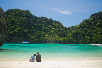love couple sitting on sand at beach and sea . Romantic time and relax at beautiful beach. honeymoon and romance concept