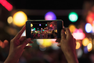 Young Asian traveler taking photo with mobile phone in pub and street road at night in Cambodia